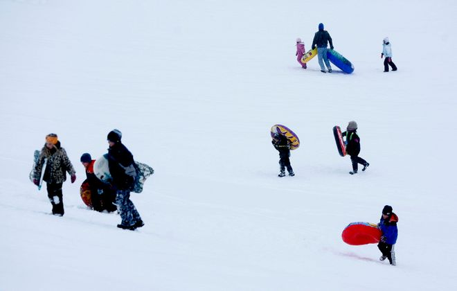 A rare sight these days. File photo of tubers walking up the hill at Elma Meadows Golf Course today in near perfect sledding conditions.     (The Buffalo News, Robert Kirkham)
