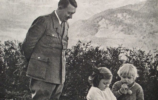 A propaganda image of Adolf Hitler looking over two children.
