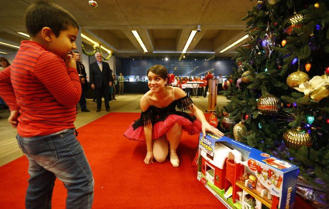 Houghton Academy student Arham Akhyar helps Neglia Ballet dancer Marie Keil place gifts under the tree during the kick-off of the News Neediest program in the lobby at The Buffalo News in Buffalo Friday, Nov. 18, 2016.  (Mark Mulville/The Buffalo News)