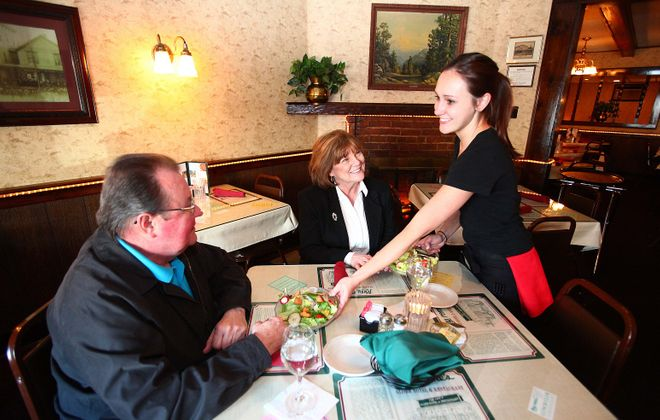 With a smile from server Mandy Munro, Ken and Colleen Kuczyk of East Aurora start off their dinner with a fresh salad at Tony Rome's Globe Hotel Restaurant in 2012. (Robert Kirkham/News file photo)