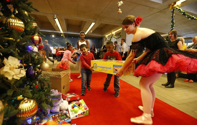 Neglia Ballet dancers Amirah Muhammad, at back, and Marie Keil get help with presents from Houghton Academy students Sanaa Ward, left, Arham Akhyar and Dallas Smith during the kickoff of this year's News Neediest drive. (Mark Mulville/Buffalo News)