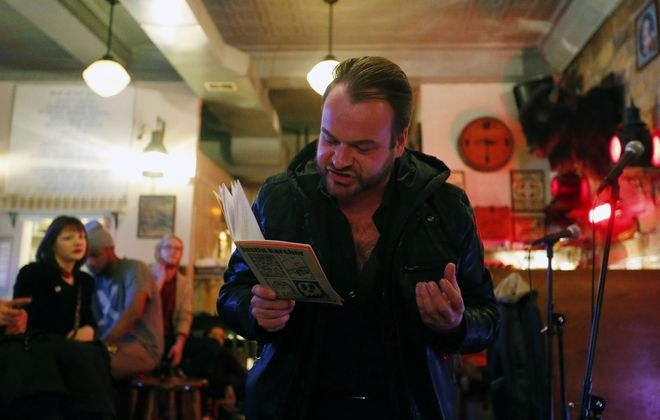 Justin Karcher reads his poetry to a gathering at The Alley Cat in Allentown. (Mark Mulville/Buffalo News)
