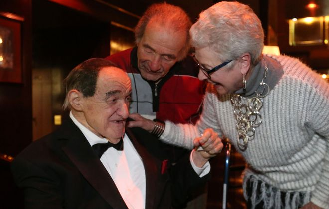 Many came out for Jackie Jocko's farewell affair at E.B. Green's restaurant where he played piano and sang for many years, Thursday, March 9, 2017. He gets a hug and a kiss from Joe Heiney, center and Salli Wagner, who have known him for 70 and 60 years, respectively, and are big fans.  (Sharon Cantillon/Buffalo News)