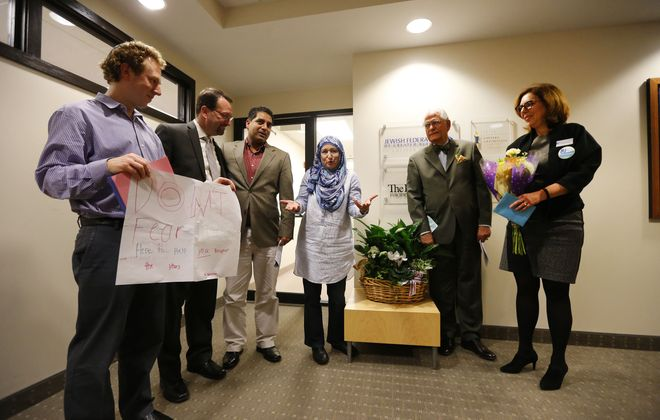 Members of the Muslim community present a gift of a plant and flowers to the Jewish community during a gathering of faith leaders at the Jewish Community Center in Getzville Tuesday, March 7, 2017. (Mark Mulville/Buffalo News)