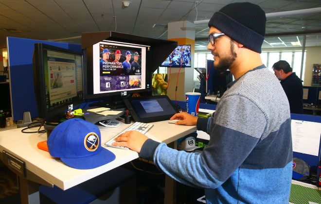 New Era is among the workplace wellness leaders in the region. Interactive graphic designer Jonathan DiRozario stands some of the time while at a workstation desk that raises and lowers. (John Hickey/News file photo)