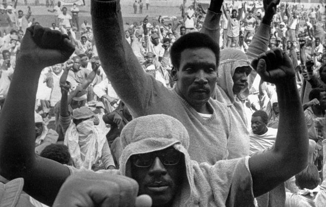 Inmates of Attica state prison in upstate New York raise their fists to show solidarity in their demands during a negotiation session with state prisons Commissioner Russell Oswald, Sept. 10, 1971.  Although amnesty was the stumbling block that derailed negotiations during the uprising 25 years ago, resulting in 43 deaths, amnesty was what nearly everyone got.  The legal battle spawned by the Attica riot continues today, and almost no one has yet been held responsible for their part in the tragedy.  (AP Photo/Bob Schutz)