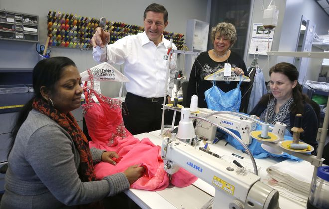 Seamstresses Damayanthi Navaneethan, left, and Lyubov Svirgun, right, work on donated prom dresses on Thursday, March 23, 2017 at Colvin Cleaners to prepare for the annual Gowns for Prom giveaway. The event is organized by Paul Billoni and his wife Cyndee, owners of Colvin Cleaners, who are standing. The work was being done at the Colvin Cleaners Elmwood Avenue location in Kenmore.  (Robert Kirkham/Buffalo News)