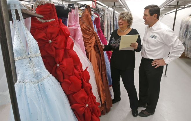 Paul Billoni and his wife Cyndee, owners of Colvin Cleaners, examine donated prom dresses in 2017. A prom gown drive is now underway.  (Robert Kirkham/Buffalo News)