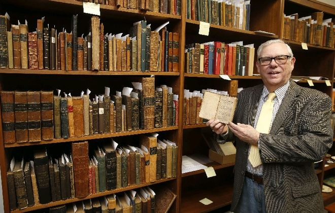"""Ronald Cozzi shows a first edition of """"The Narrative of the Life of Mary Jamison"""" from the early 1800s that is in the collection at his Old Editions Book Shop in Buffalo. (Robert Kirkham/Buffalo News)"""