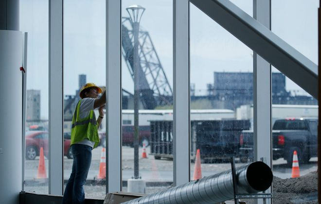 Workers weatherproof the glass facade of the offices on the north end of the building as construction continues at the massive Solar City manufacturing facility at RiverBend, Wednesday, May 11, 2016. (Derek Gee/Buffalo News)
