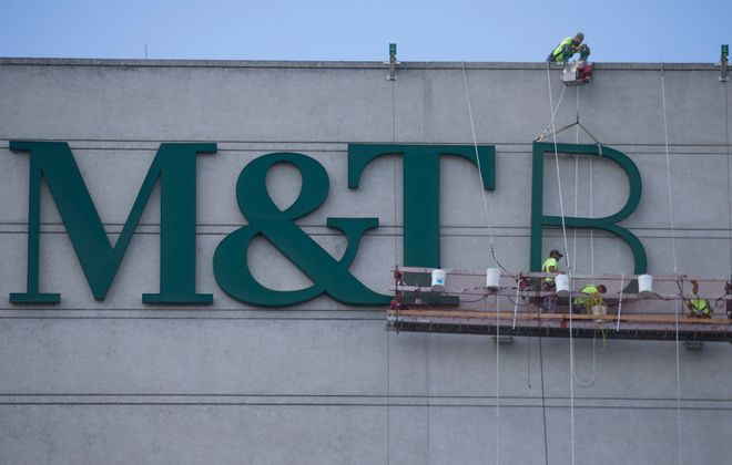 """Workers install the """"B"""" for the M&T Bank sign at its Main Street headquarters last summer. Under Chairman and CEO Robert G. Wilmers, the bank has seen steady growth, most recently through its acquisition of Hudson City Bancorp. (John Hickey/Buffalo News)"""