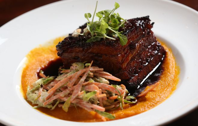 Black & Blue's pork belly starter is sweet and spicy braised pork belly with a brussels sprout slaw, carrot-ginger puree and cashews. (Sharon Cantillon/Buffalo News)