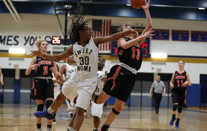 Amherst's Claire Wanzer is fouled by Sweet Home's Brianna Millender during first half action at Sweet Home high school on Tuesday. (Harry Scull Jr./Buffalo News)
