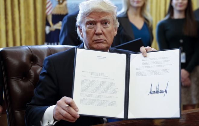 President Donald Trump displays one of five executive orders he signed in the oval office of the White House on Jan. 24, 2017 (Getty Images)