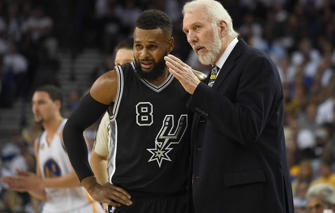 San Antonio coach Gregg Popovich talks with Patty Mills during the Spurs' season-opening rout of the Warriors in Oakland. (Getty Images)