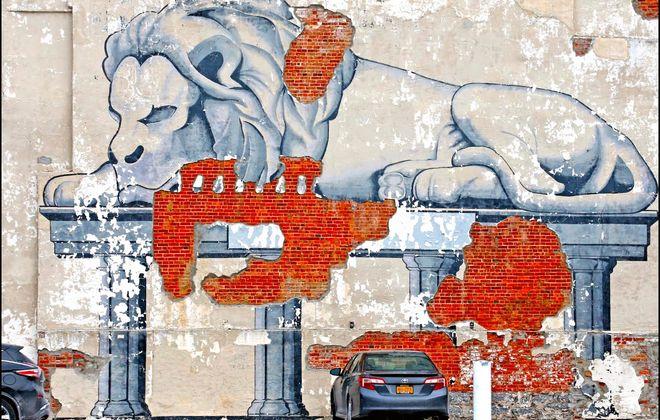 Frank Cravotta's mural of a lion at the corner of Delaware Ave. and Allen St. has seen better days.  (Robert Kirkham/Buffalo News)