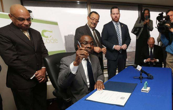 Mayor Byron Brown signs the Green Code into law at Seneca One Tower. It's the first major overhaul to city zoning laws since 1953. (Sharon Cantillon/Buffalo News)