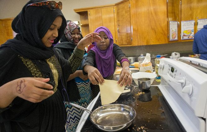 From left, Hamda Driri, 15, Maria Musa, 17, and Nasra Ali, 15, make sambusas, an African flatbread, during a cooking class at Lafayette High School's Saturday academy program. (Derek Gee/Buffalo News)