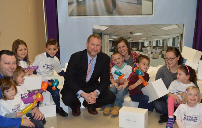 Sisters of Charity Hospital President and CEO Peter Bergmann, center, announced plans for a new $8.8 million neonatal intensive care unit alongside some of children born in the existing NICU, and their parents.