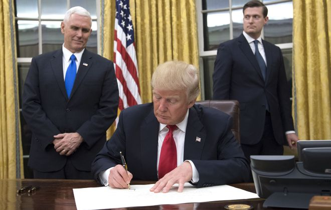 President Trump signs documents in the Oval Office. (Getty Images)
