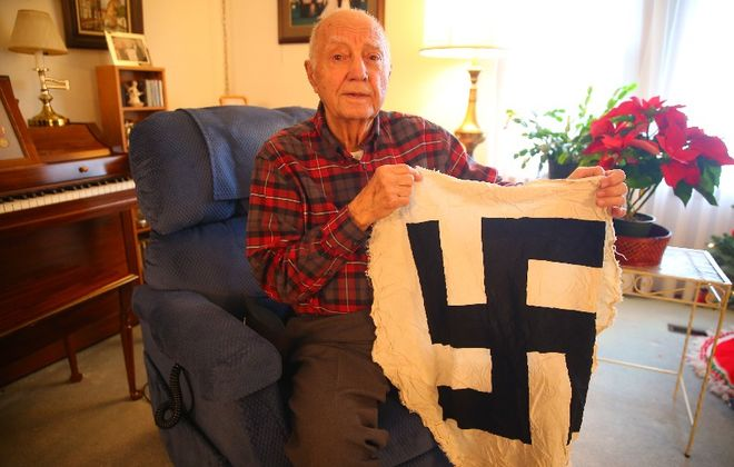 Michael A. Altieri Sr. displays a section of Nazi flag he took from a base in Erlanger, Germany, during Word War II. His unit chased retreating Germans but couldn't catch up with them. (John Hickey/Buffalo News)