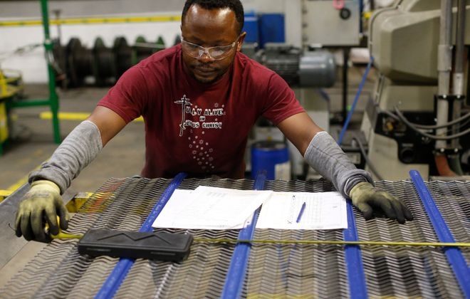 Babingwa Watimbwa Olivier, a refugee from the Democratic People's Republic of Congo, inspects a screen as it comes off a production line at Buffalo Wire Works.  (Derek Gee/Buffalo News file photo)