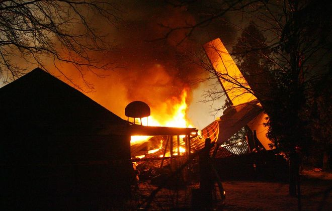 The wreckage of Flight 3407 and the home it crashed into in Clarence Center burn the night of Feb. 12, 2009. (News file photo)