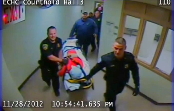In this frame from the Holding Center video, jail guards escort the inert form of inmate Richard Metcalf to an ambulance.