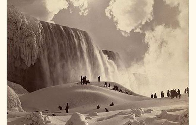 People walk on the Niagara Falls ice bridge at the base of the American Falls in 1883. Until the tragedy in 1912, this was a popular way of viewing the falls. (Photo courtesy of the Library of Congress)