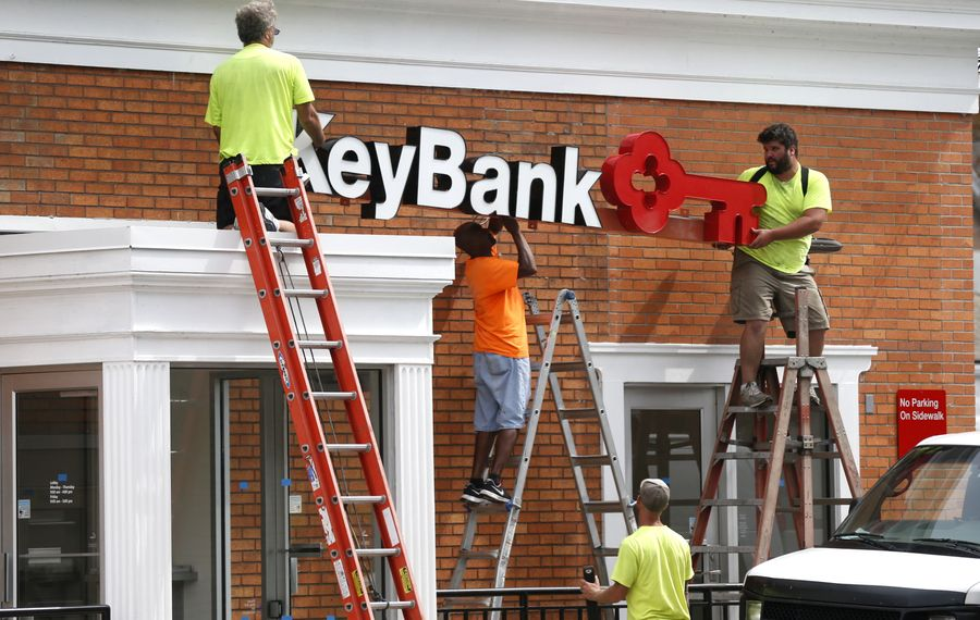 Contractors install a KeyBank sign after removing a First Niagara logo on the bank branch at the corner of Willett and Clinton streets in Buffalo shortly after the acquisition.  (Robert Kirkham/News file photo)