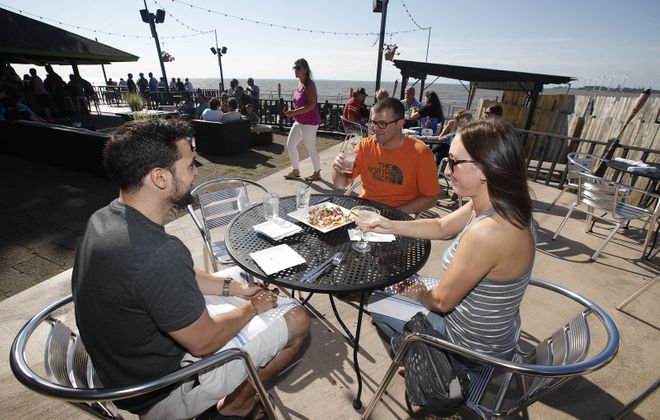 Hanging out at Dos Amigos' patio, from left, are Lockport native Phil Carlisle, of Dallas, and Erik and Lindsey Solem, of Buffalo. (Sharon Cantillon/Buffalo News)