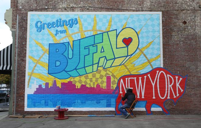 """Artist Casey William Milbrand works on his colorful """"Greetings from Buffalo"""" mural in 2016.(Sharon Cantillon/Buffalo News)"""
