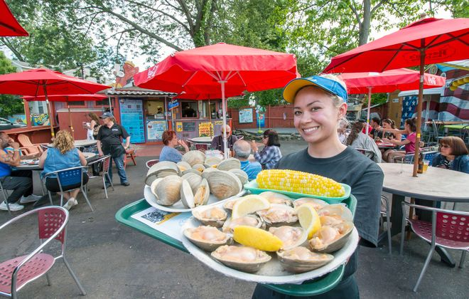Rene Hudson delivers a selection of raw and steamed clams to customers at Old Man River in Tonawanda. (Dave Jarosz)