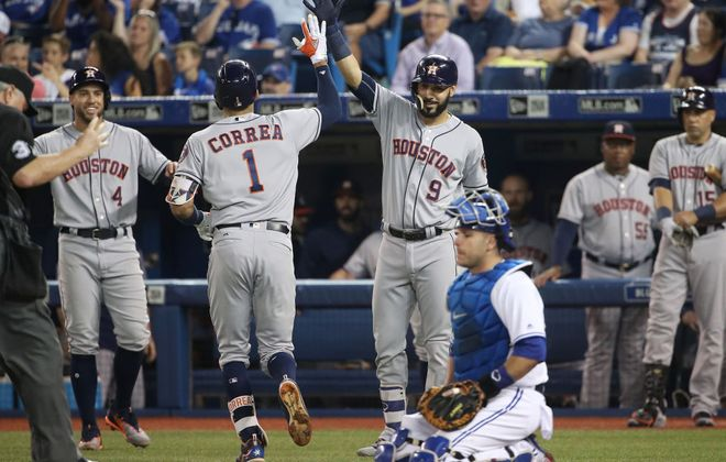 George Springer (4) and Marwin Gonzalez (9) greet Carlos Correa after he belted a first-inning homer Friday in Toronto (Getty Images).