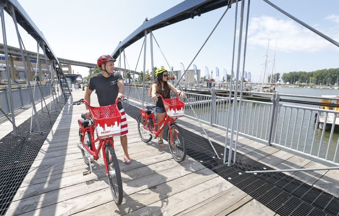 Austin Bobeck, left, of Cheektowaga, and his girldriend Mabel Integro, of West Seneca explore around CanalSide with their rented Reddy Bikes on Monday, July 24, 2017.  (Robert Kirkham/Buffalo News)