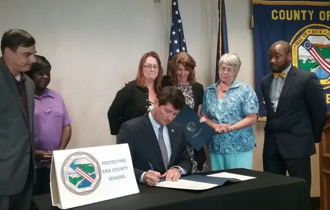 It was an emotional moment when Erie County Executive Mark Poloncarz signed Ruthie's Law in July 2017, as Ruth Murray's daughters watched. But nursing homes say the law is illegal and unenforceable. (Photo courtesy of Erie County)