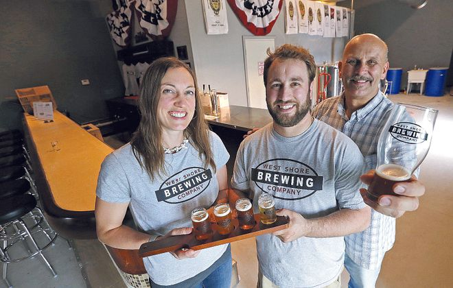 West Shore Brewing Company owners, from left, Laura, Josh and Greg Dziomba, have opened the first brewery in Clarence, at 10995 Main St., next door to Antique World & Flea Market. (Robert Kirkham/Buffalo News)