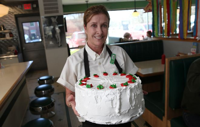 Uncle Joe's Diner server Melissa Vogler shows off the strawberry volcano cake made by Melanie's Eats-N-Sweets. (Sharon Cantillon/Buffalo News)