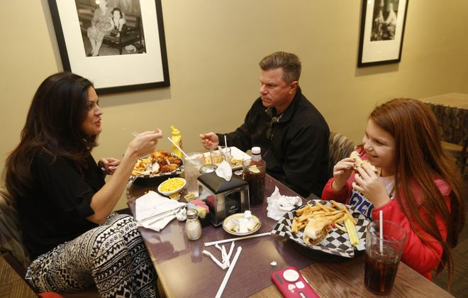 Regulars Elaine and Michael Connelly and their daughter Grace, all of West Seneca, have dinner at Christes Restaurant.  (Sharon Cantillon/Buffalo News)