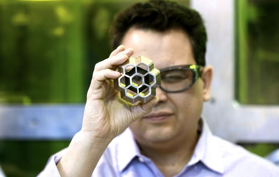 Frank Medina, technology leader for additive manufacturing, examines a piece made on a 3D printers at Buffalo Manufacturing Works. (Robert Kirkham/Buffalo News)