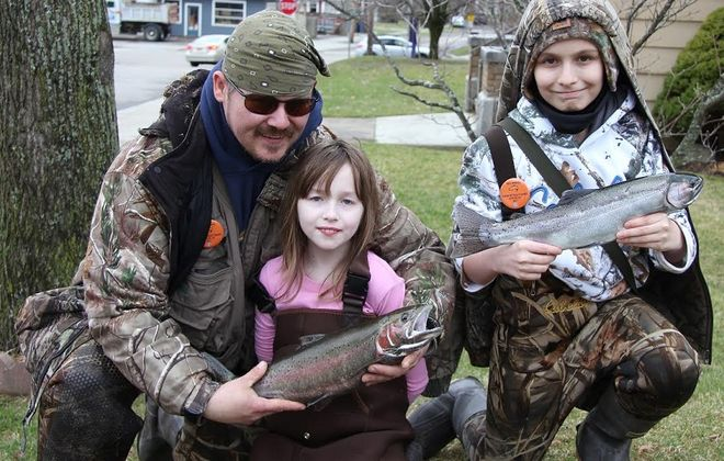 "Thomas Pustulka of Buffalo with his daughter Illyanna and nephew Camren with the fish they caught during the 56th Annual Opening Day Naples Rainbow Trout Fishing Derby. Illyanna won the ""Girls Under 16 Years Division with her 2.60- pound rainbow."