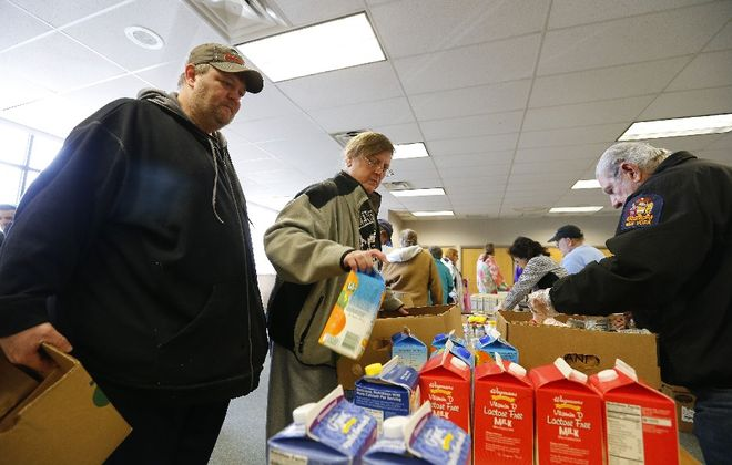 Keith and Bobby Muhlenbeck select free groceries at the food bank run by Community Action for Wyoming County. They support President Trump even though his budget threatens programs like this. (Mark Mulville/Buffalo News)
