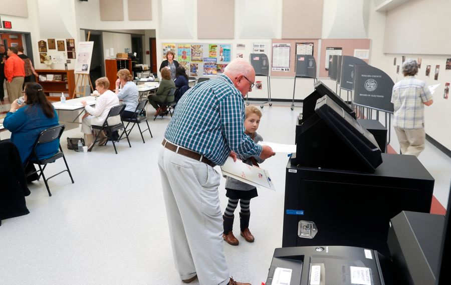 Joe Brzezinski votes on  the  Starpoint school budget with his granddaughter  Zoe Zewiskey, 5, in the   Starpoint High School Tuesday.  (John Hickey/Buffalo News)