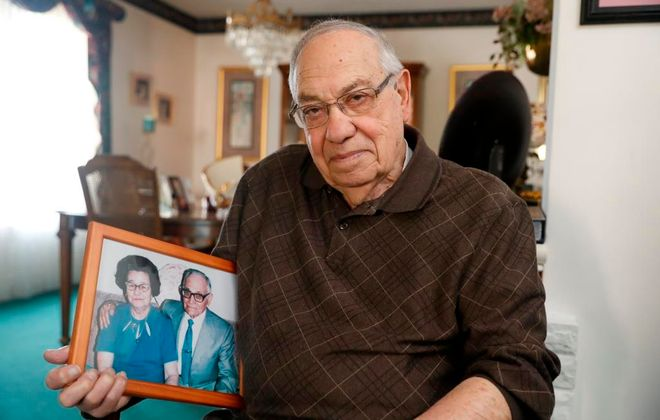Mario Pirastru, holding an image of his mother and father, Giovana and Luigi, at his home in Niagara Falls. Thirty years ago, Mario offered timeless advice about the relationship all mothers have with their children. (John Hickey/Buffalo News)