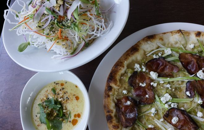 A bacon pizza with parmesan cream, scallion, leeks and lemon-chive goat cheese, a bowl of coconut and corn soup and the Singapore slaw at Roost. (Derek Gee/Buffalo News)