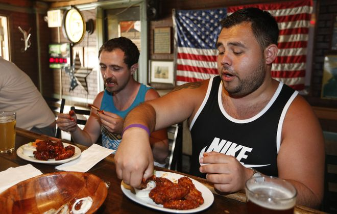 Mike Bueme, left, of Cheektowaga, enjoys the BBQ hot wings while Corey Spruce of Blasdell has the extra hot garlic wings. (Sharon Cantillon/Buffalo News)