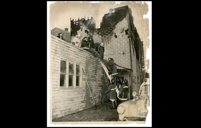 In this photo from Nov. 16, 1957, firefighters remove the body of one of the 18 people, most of them children from the Reid and Ewing families, who died when fire ripped through the condemned Moonglow Hotel on Allen Avenue in Niagara Falls. The Ewing family members have been commemorated by Oakwood Cemetery, where they are buried.