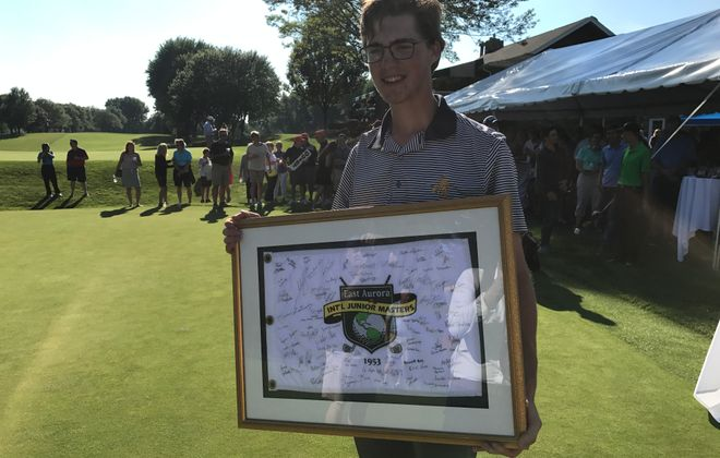 Danny Gianniny holds a framed flag signed by all 80 participants after winning the International Junior Masters. (Matt Schneidman/The Buffalo News)