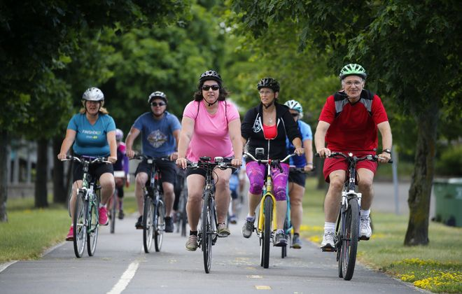 Shirley Carnall (pink shirt) is a group host with the Buffalo Outdoor Meetup group. She leads a bike ride along the Niagara River on Tuesday in the Town of Tonawanda. (Mark Mulville/Buffalo News)