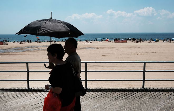 An umbrella helps beat the heat along the boardwalk on Coney Island. Airplanes are a different matter. (Photo by Spencer Platt/Getty Images)